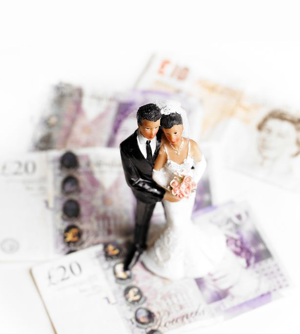 0_Bride-and-groom-wedding-figures-standing-on-a-pile-of-banknotes-Concept-of-the-cost-of-weddingspre.jpg