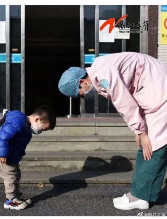 Phía sau bức ảnh cảm động cậu bé 2 tuổi cúi đầu trước bác sĩ chống dịch SARS-CoV-2 - Ảnh 1.