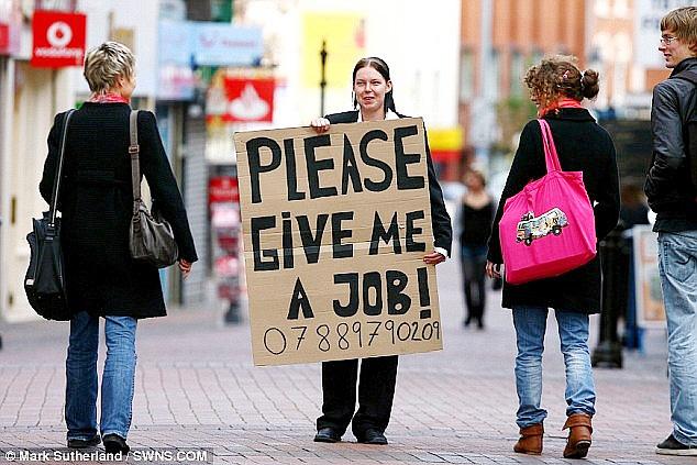 Một phụ nữ đeo bảng xin việc trên đường phố