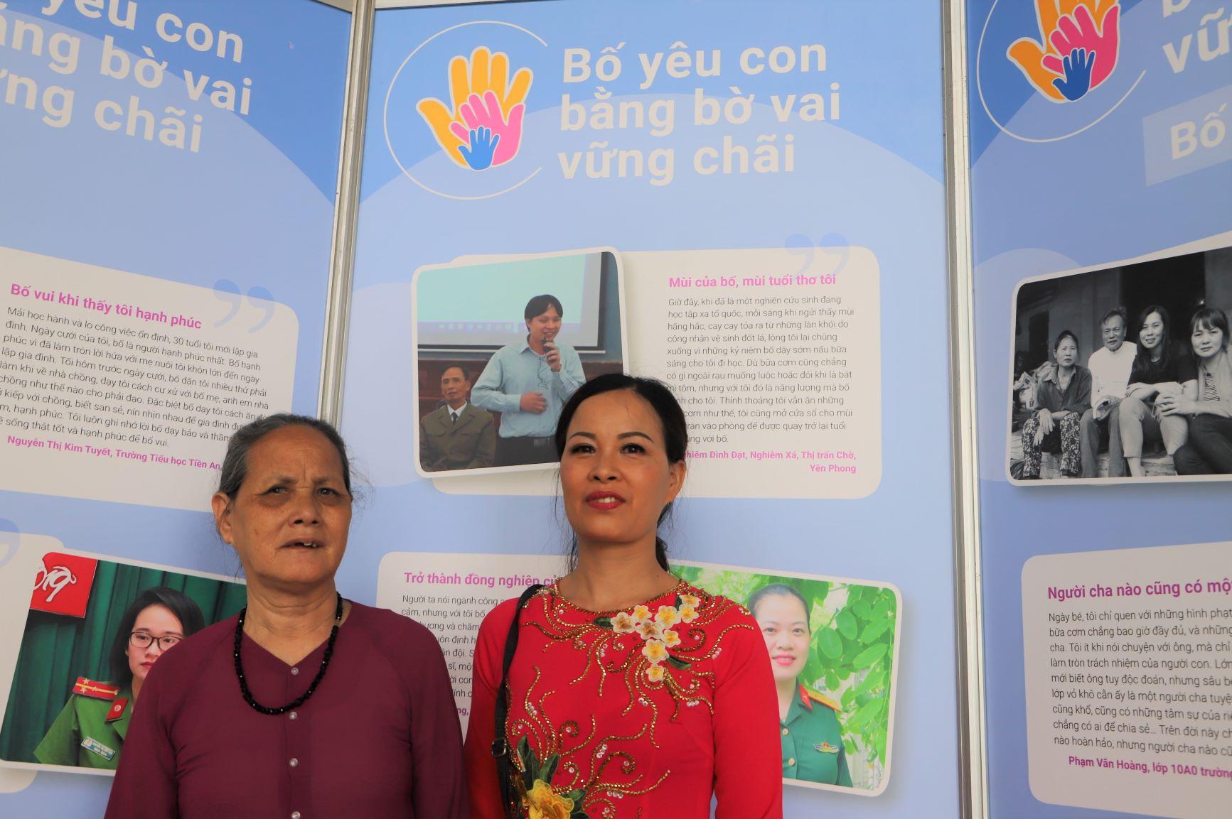 Bà Nghiêm Thị Tứ cùng con gái đến tham dự triển lãm. Con trai của bà là anh Nghiêm Đình Đạt (hình ảnh triển lãm ở phía sau lưng bà) là người đoạt giải nhất tại cuộc thi viết