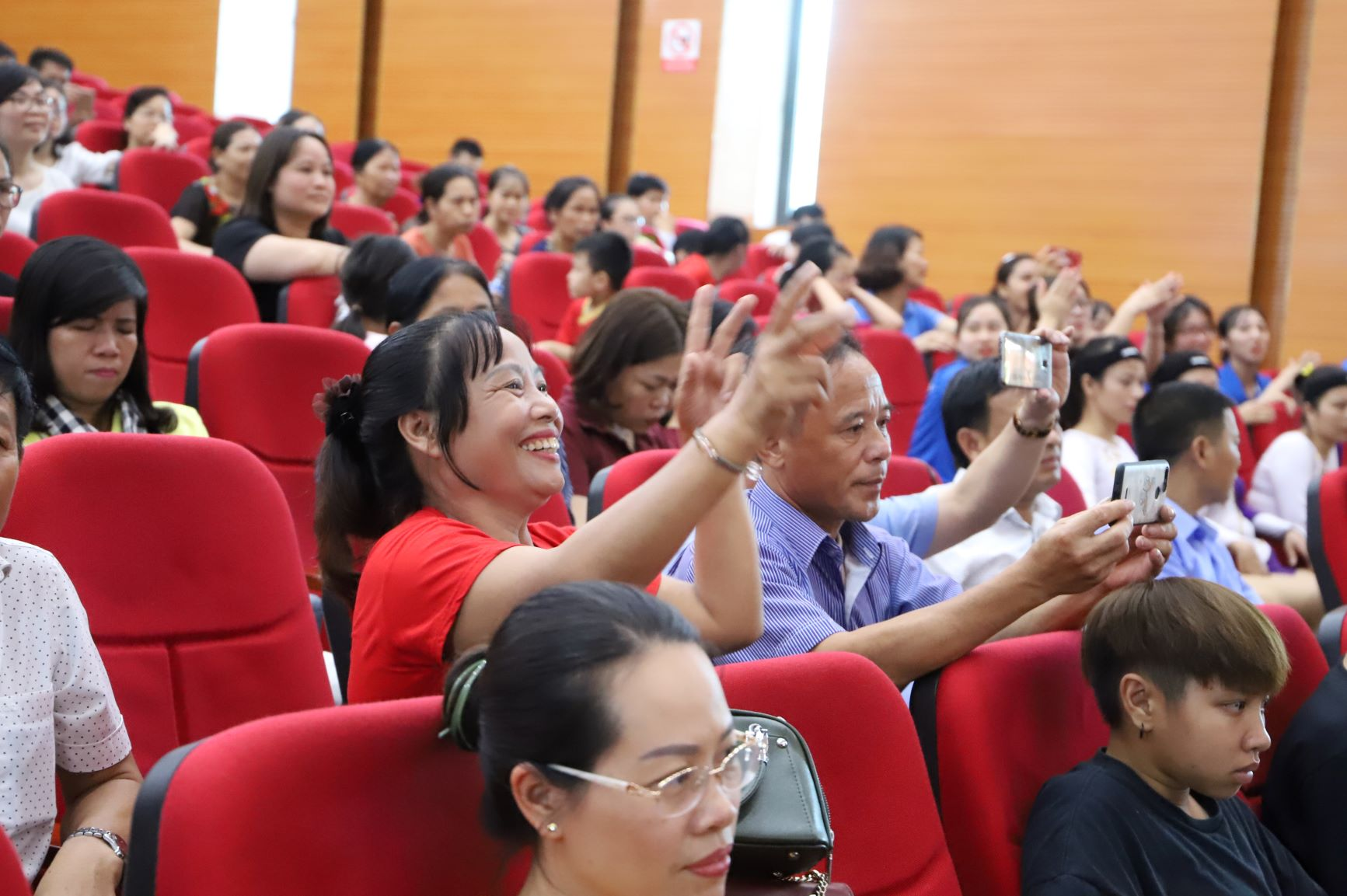 Nụ cười thích thú của một nữ khán giả khi đội nhà có màn trình diễn gây ấn tượng tại cuộc thi nhảy dân vũ và aerobic.