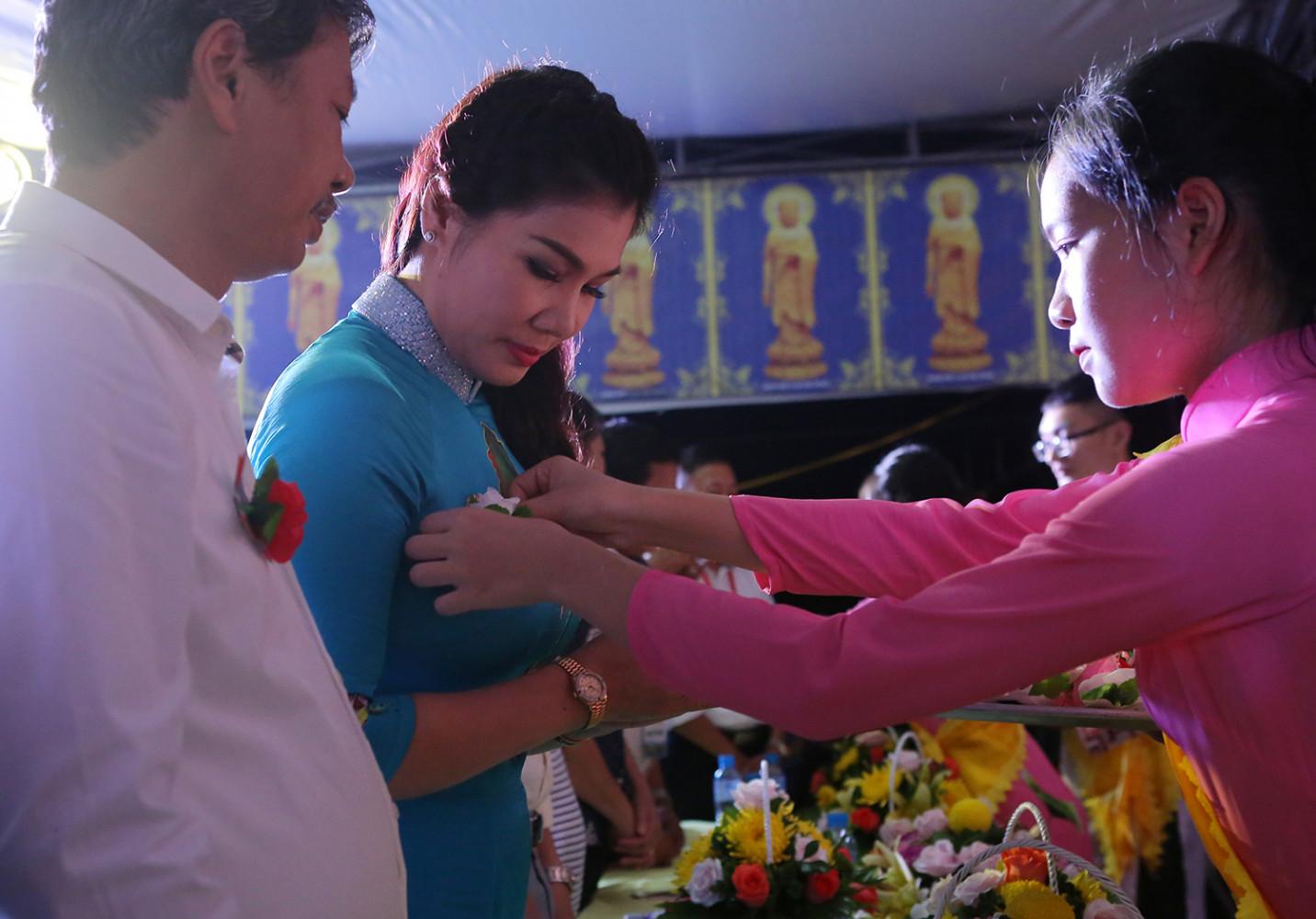 Các phật tử cài hoa trên ngực cho các đại biểu dự Lễ Vu lan Báo hiếu.