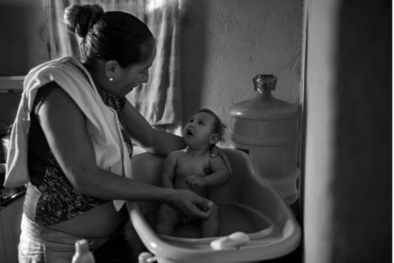 """Trước khi sinh Gilberto, bà Gomes nấu ăn và lau dọn ở một nhà hàng. Hiện tại, nguồn thu nhập duy nhất của bà là khoản tiền hỗ trợ hằng tháng của Chính phủ dành cho những gia đình nghèo. Bà được nhận khoảng 130 đô la Mỹ mỗi tháng.  Bà phải ngủ chung với các con vì không có đủ giường. Họ không có điều hòa, không có nước uống. Muỗi bay khắp nơi.  """"Thi thoảng, tôi cũng muốn dọn ra khỏi nơi này. Nhưng tiền thuê nhà ở đây khá rẻ, chưa tới 40 đô la Mỹ một tháng"""". Bệnh viện khuyến khích bà Gomes đăng ký nhận trợ cấp dành cho các gia đình có con bị dị tật. Thế nhưng, quá trình đăng ký cũng khá phức tạp và bà đang phải chỉnh sửa một lỗi sai nhỏ trên giấy khai sinh của một cậu con trai. Khi bà hết tiền, bà xin bỉm và sữa tắm cho em bé ở phòng dự trữ của bệnh viện. Từ khi dịch Zika bắt đầu, rất nhiều người đã quyết định quyên góp.  Bà đã từng cảm thấy xấu hổ khi cầu tới sự giúp đỡ của người khác. Thế nhưng bây giờ, bà nói, bà sẵn sàng nhờ vả bất cứ ai. """"Tôi là bố của Gilberto"""" - bà nói - """"Giờ tôi vừa là bố, vừa là mẹ của thằng bé""""."""