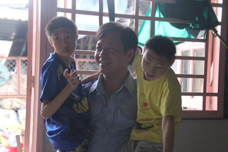 Trong căn phòng nhỏ được dựng tạm bợ bằng những tấm tôn cũ ghép lại ở số 12B/45, đường liên ấp 123, xã Vĩnh Lộc B, huyện Bình Chánh, ba cha con anh Đặng Hữu Nghị đang chơi đùa cùng nhau ở giữa nhà.