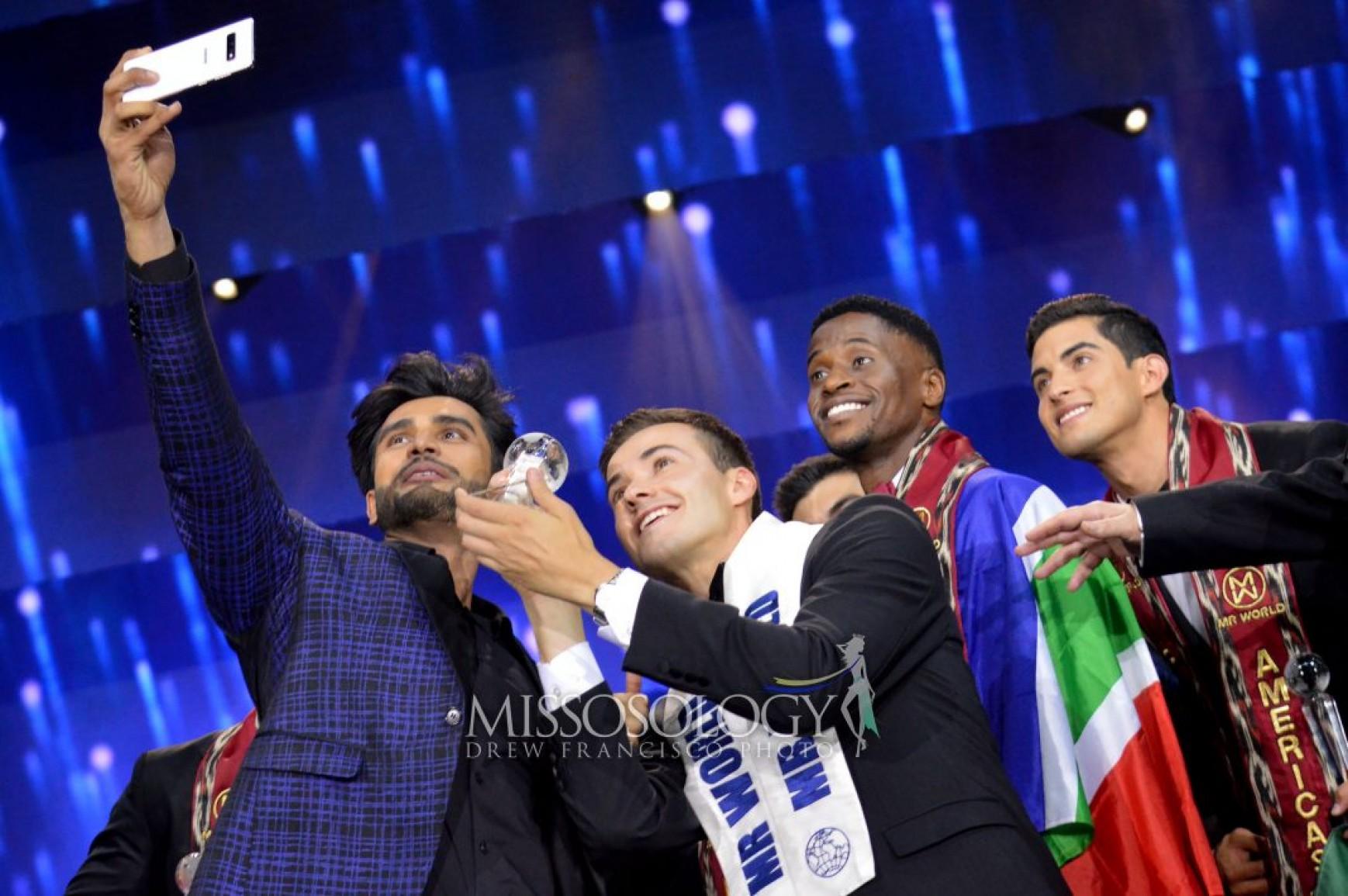 Tân Nam vương Thế giới vui vẻ selfie cùng các thí sinh. Cuộc thi Nam vương Thế giới - Mr World mặc dù ra đời từ năm 1996 nhưng đến nay mới chỉ tổ chức được 10 lần. Cuộc thi này thuộc quyền quản lý của nhà tổ chức Hoa hậu Thế giới - Miss World, vì thế Nam vương và Hoa hậu Thế giới sẽ là những đại sứ cho các hoạt động