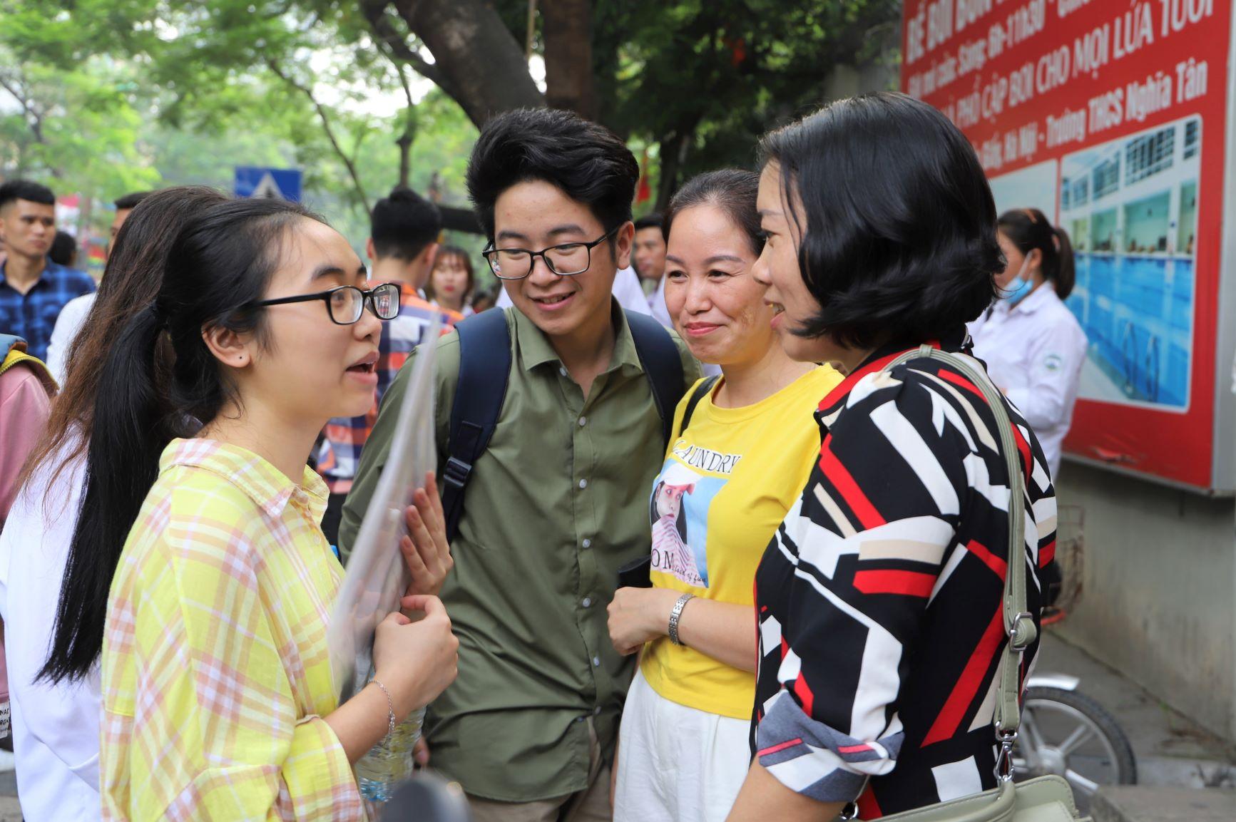 Nhóm phụ huynh, học sinh đứng túm tụm ngay trước cổng trường để trao đổi về kết quả thi. Ai cũng nở nụ cười