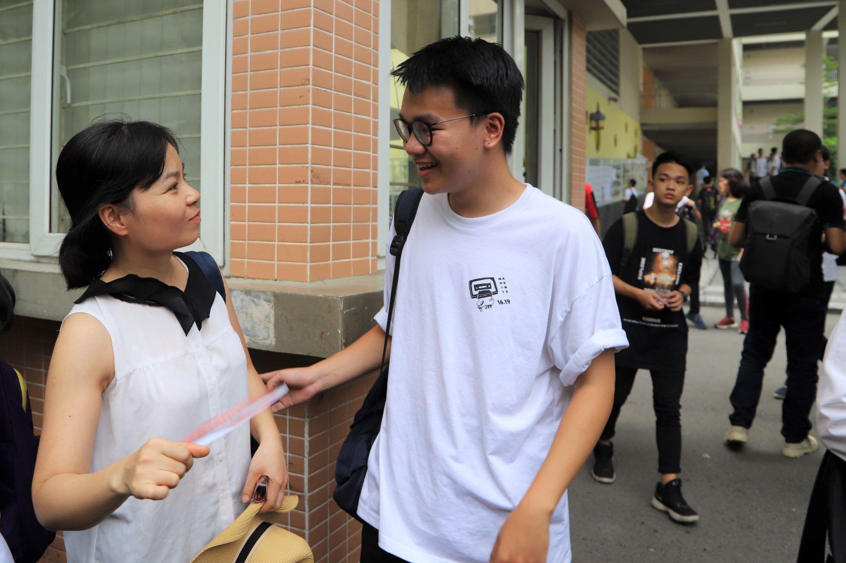 Nữ phụ huynh đón con ngay ở cổng trường, tay không quên quạt cho con được mát hơn sau buổi thi căng thẳng