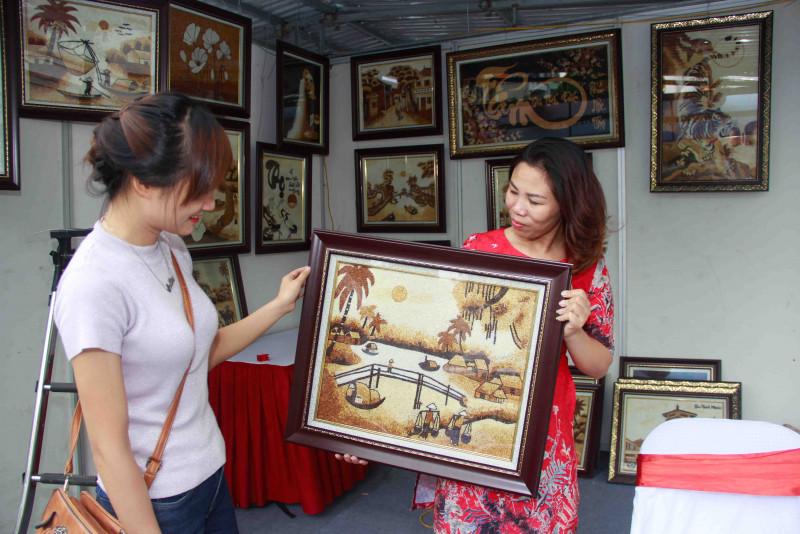 Còn chị Nguyễn Thị Vân (bên phải), ở xã Đông Xuân, huyện Sóc Sơn, Hà Nội, nhờ nguồn vốn vay từ TYM, đã đầu tư mua vật tư như khung gỗ, kính, gạo... để làm ra những bức tranh gạo độc đáo, sáng tạo và đẹp mắt.