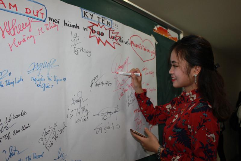 Một nữ sinh ký tên hưởng ứng thông điệp Sinh viên Học viện Phụ nữ Việt Nam phản đối mọi hành vi bạo lực đối với phụ nữ và trẻ em gái.