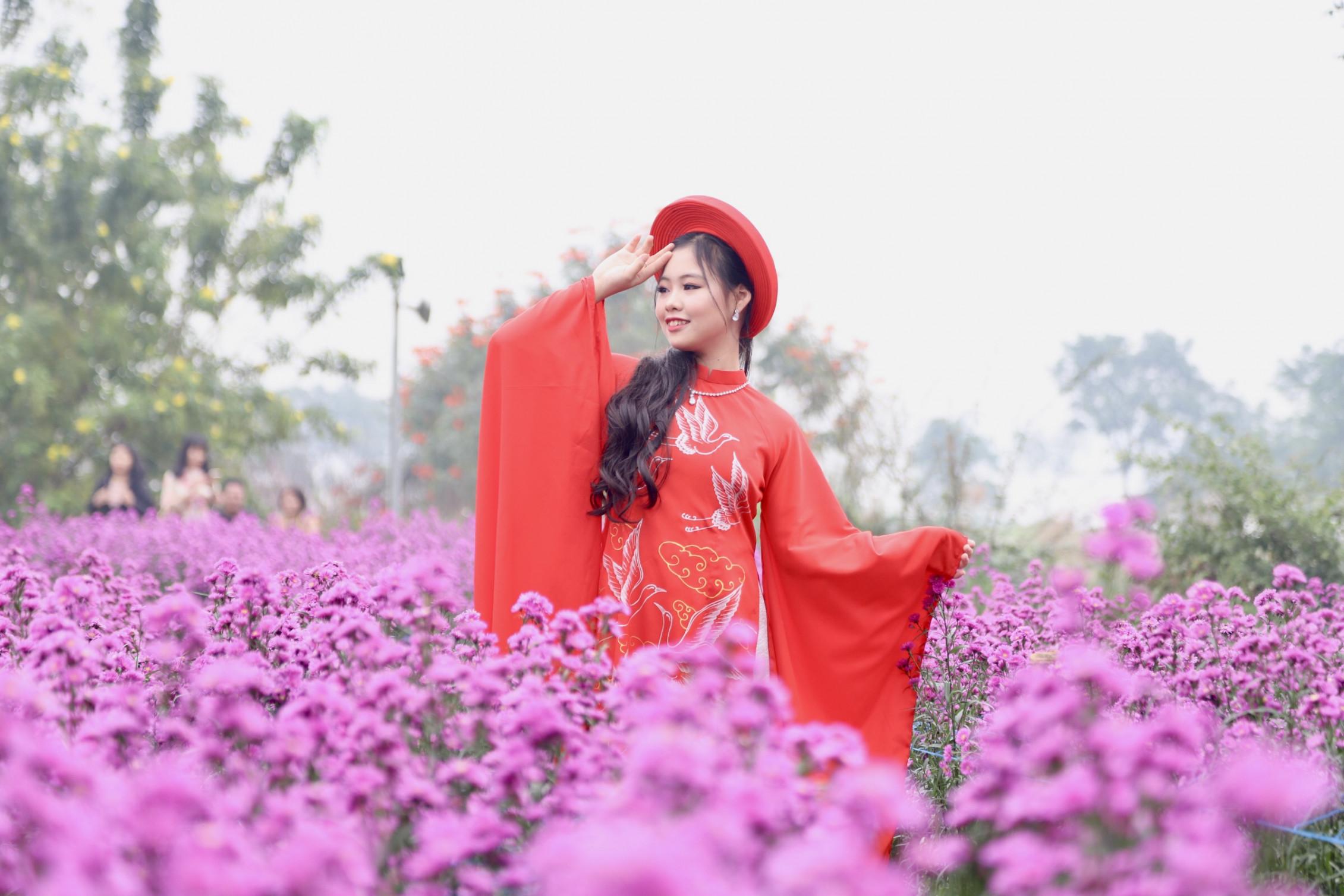 Trong bộ áo dài Quốc phục màu đỏ rực rỡ, mẫu nhí Đỗ Bảo Chi tạo dáng trên cánh đồng hoa tím. Trông cô bé giống như đang múa một điệu múa thần tiên. Bảo Chi sinh năm 2006, hiện sống tại Bắc Ninh. Với khuôn mặt xinh xắn, giọng hát hay và những bước catwalk tự tin, Bảo Chi nhận được rất nhiều lời mời trình diễn.