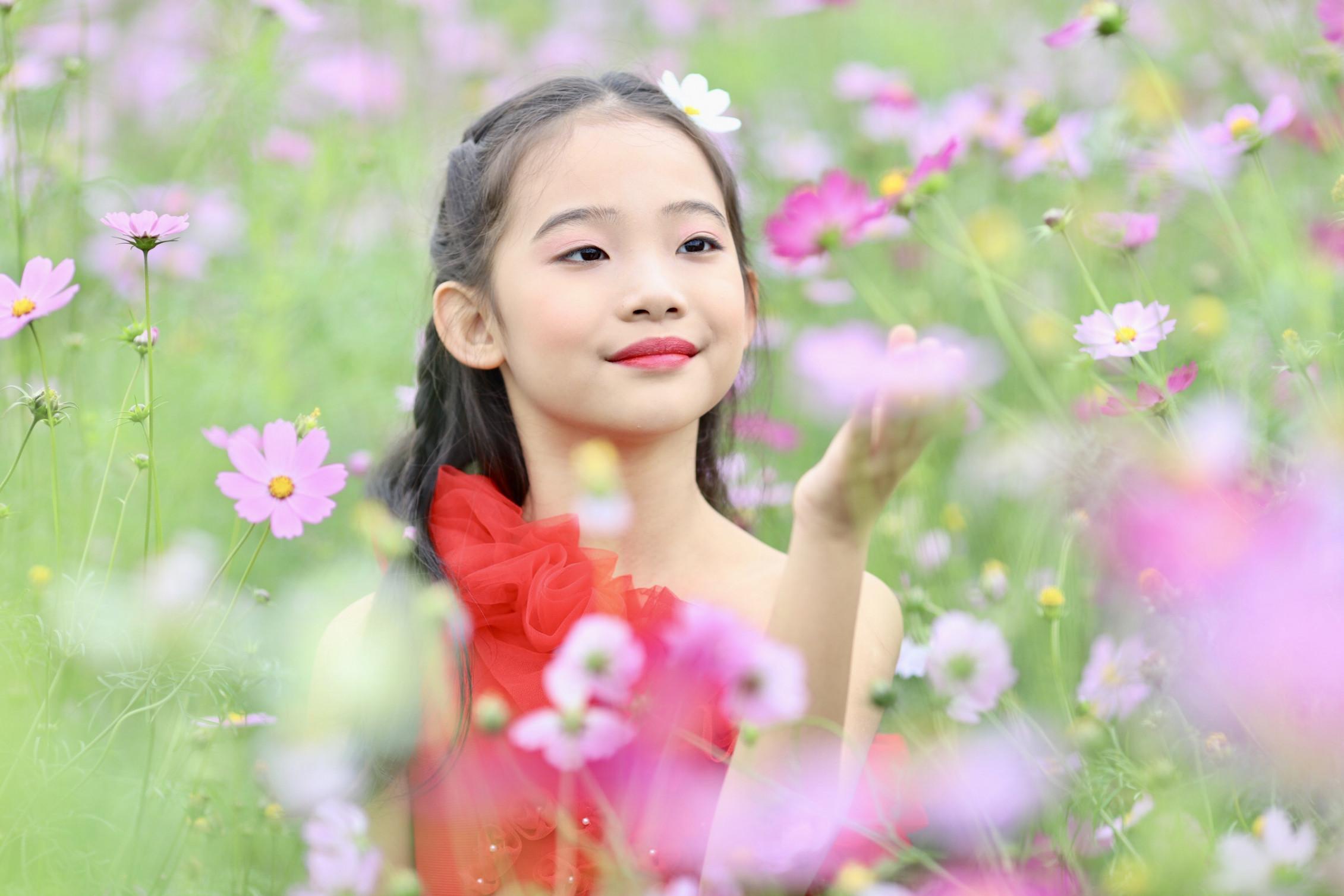 Trên cánh đồng hoa sao nhái, mẫu nhí Hà Phương giống một cô tiên xuân trong bộ váy màu đỏ rực rỡ. Hà Phương sinh năm 2009, là 1 trong 3 thành viên của Nhóm uốn dẻo Emmy - Quán quân Tìm kiếm tài năng nhí Ngôi Sao Hướng Dương 2018.