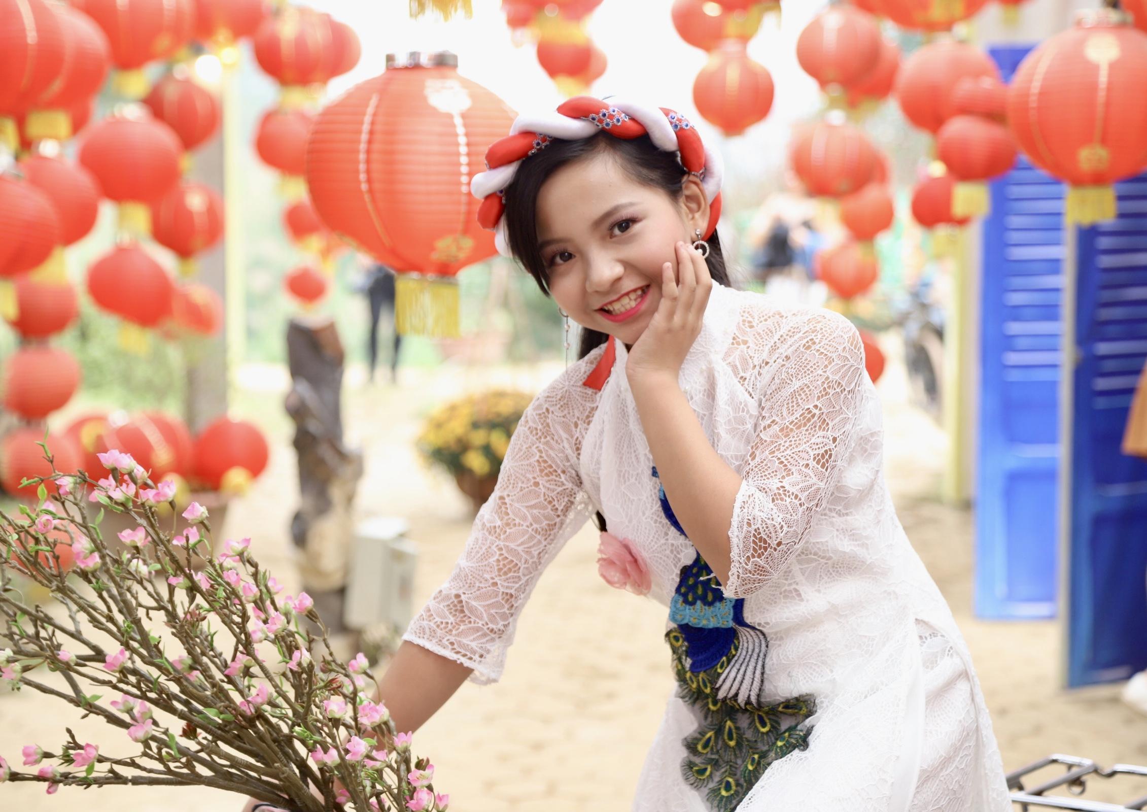 Với bộ áo dài cách tân màu trắng và chiếc vấn đầu xinh xắn, ca sĩ nhí Đinh Trần Khánh Vy chào xuân mới bằng nụ cười rạng rỡ. Đinh Trần Khánh Vy sinh năm 2007, cô bé từng đạt giải Quán quân cuộc thi Tìm kiếm tài năng nhí Ngôi Sao Hướng Dương mùa đầu tiên.