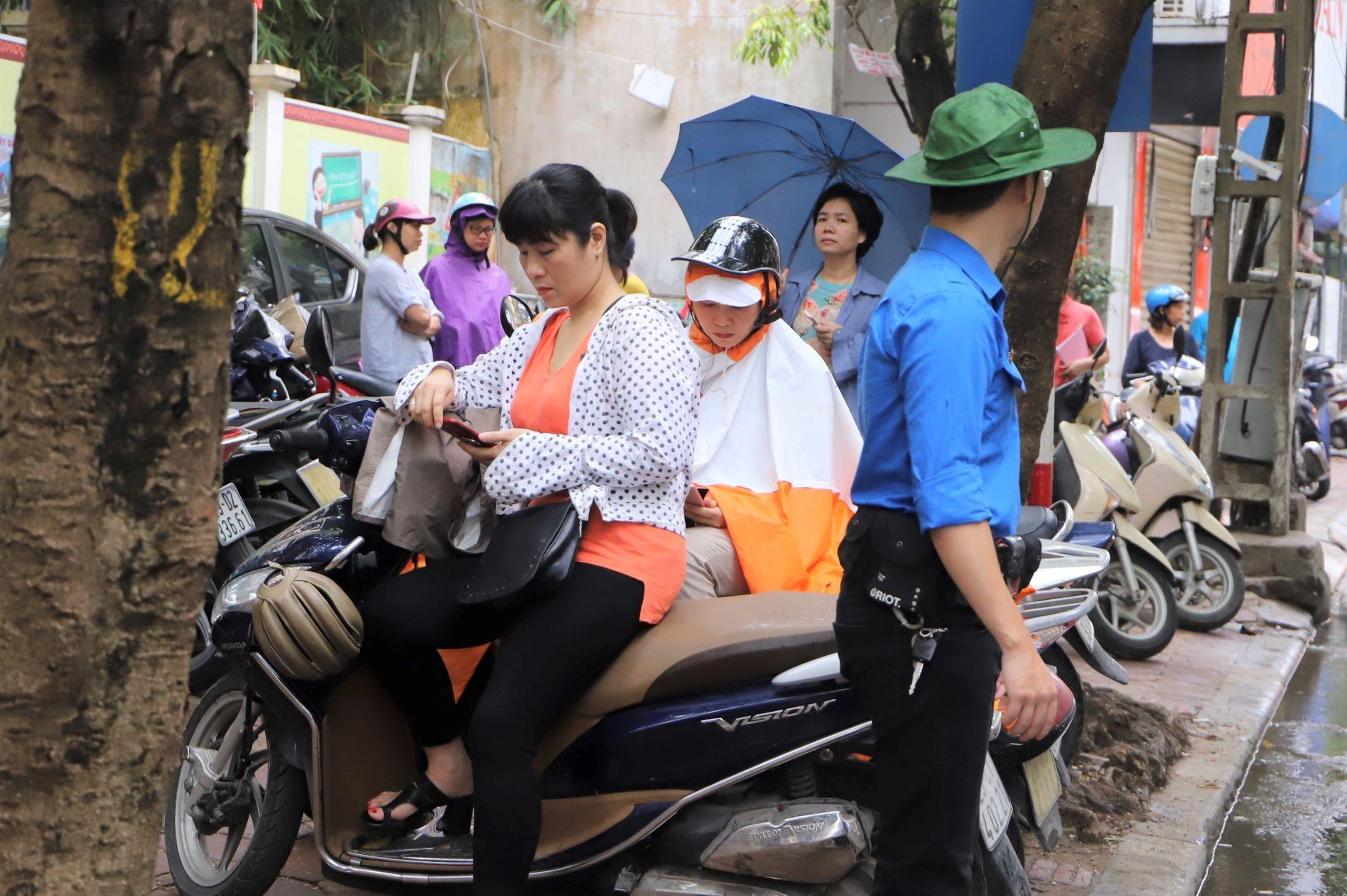 Điểm thi THCS Chu Văn An khá chật chội nên phụ huynh chật vật tìm chỗ ngồi, tranh thủ lướt điện thoại cho đỡ sốt ruột