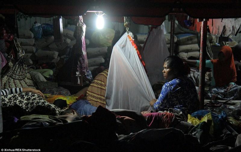 Một người phụ nữ thức đêm trông con, trong khi những người khác cố đi vào giấc ngủ sau sự mệt mỏi và sợ hãi mà động đất gây ra.