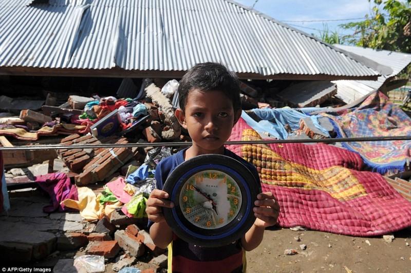 Cậu bé Faizal, 8 tuổi, cầm trên tay chiếc đồng hồ chỉ thời gian xảy ra động đất tại ngôi làng Kuta Pangwa, Indonesia. Toàn bộ nhà cửa của gia đình cậu bé sau đó đã bị san phẳng.