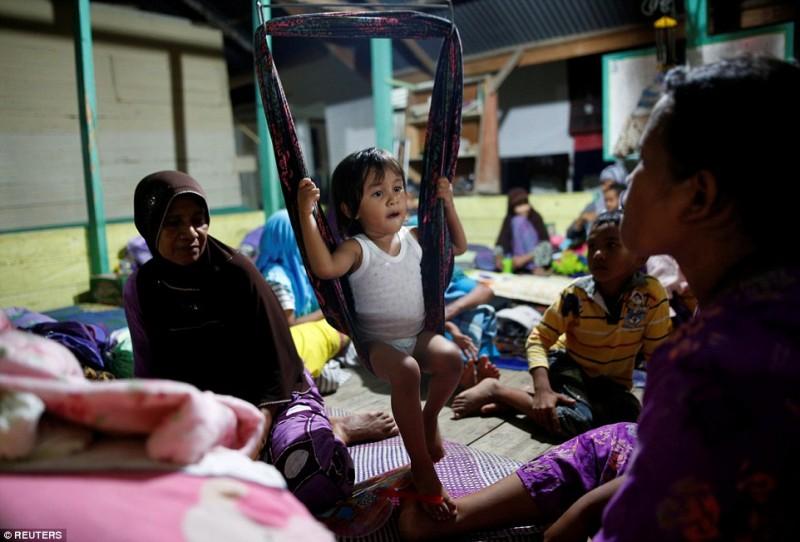 Người dân đưa con em mình đến các ngôi nhà ở tạm tại các trường học, sau khi trận động đất 6,5 độ richter biến họ trở thành người vô gia cư.