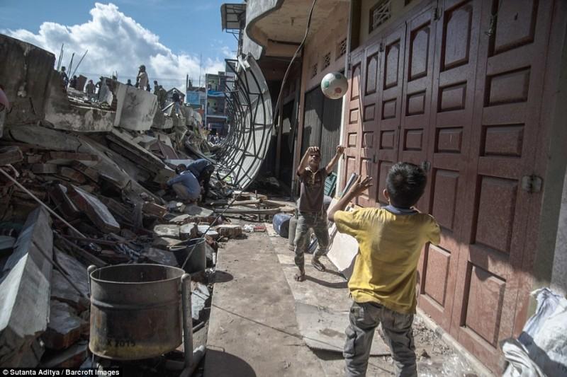 Hai cậu bé chơi bóng bên cạnh tòa nhà đổ nát tại huyện Pidie Jaya, tỉnh Aceh của Indonesia.