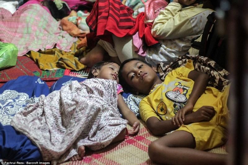 Các em bé mất đi nhà cửa nằm tụm lại với nhau trong ngôi nhà ở tạm cùng với gia đình của mình.