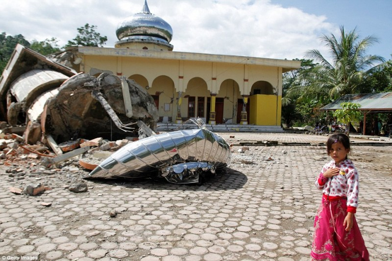 Một em bé đi ngang qua tòa nhà bị sụp đổ, không giấu vẻ lo lắng, đau lòng.