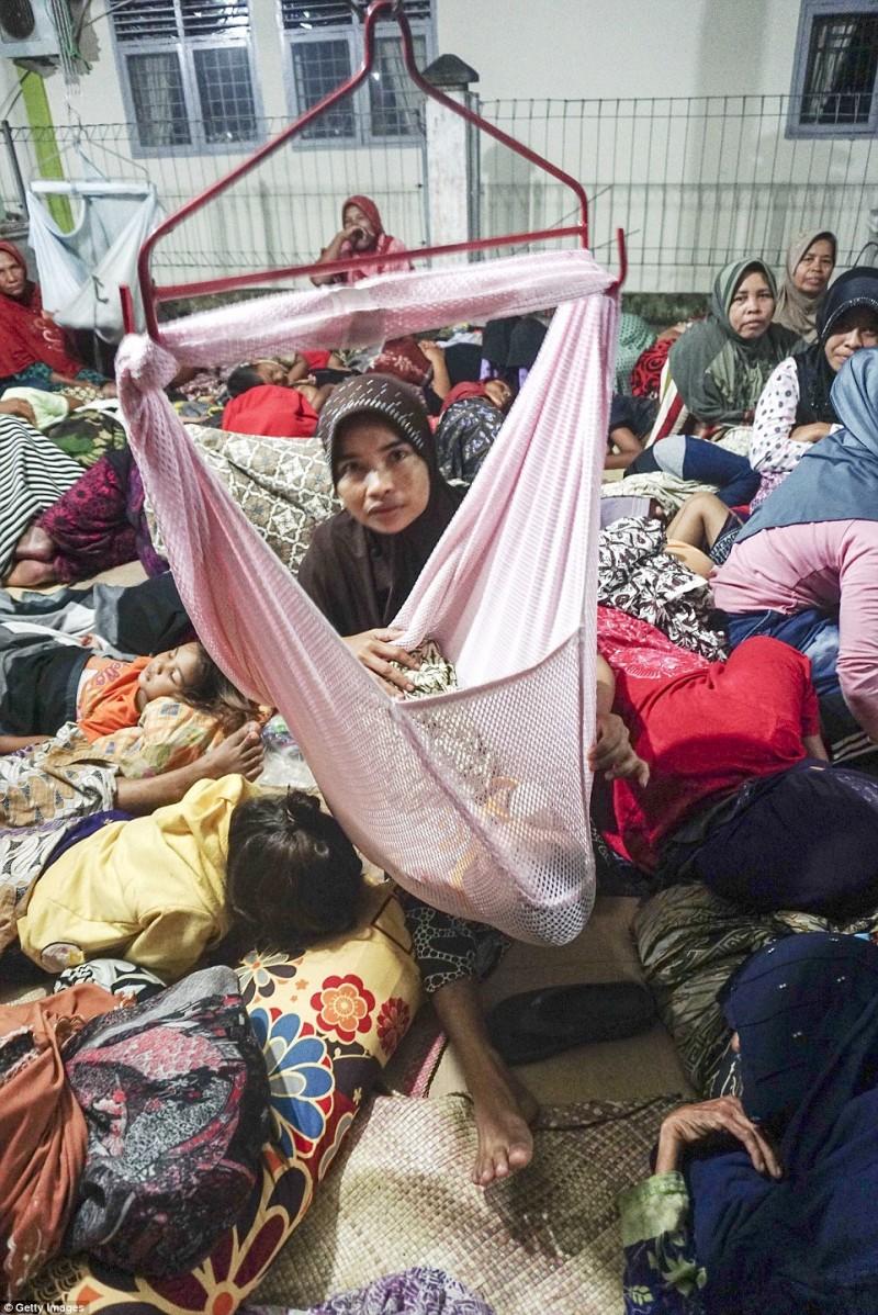 Một người mẹ để con mình ngủ trong chiếc võng tự chế, xung quanh là biển người đang lo sợ dư chấn mà không thể ngủ được.