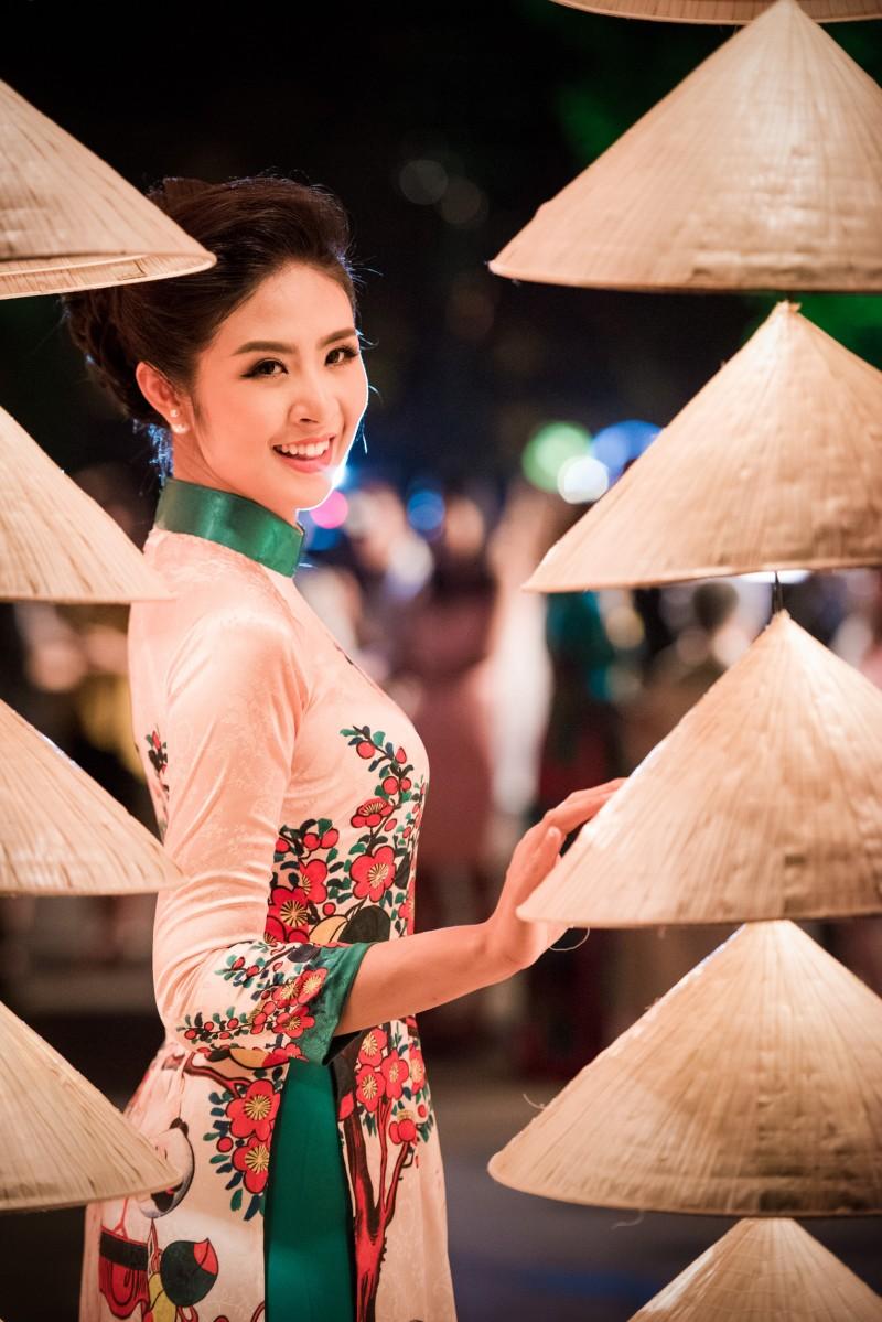 Hoa hậu tranh thủ tạo dáng bên những chiếc nón trang trí cho buổi trình diễn áo dài công bố Festival Áo dài Hà Nội 2016.