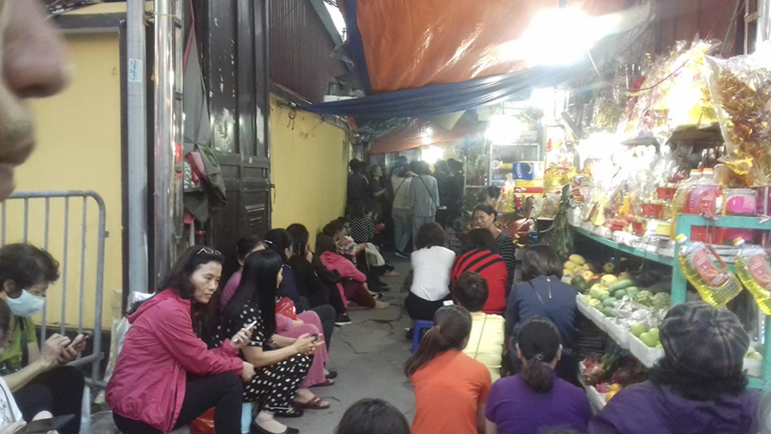 Không được vào bên trong, nhiều người bắt đầu ngồi dọc lối đi vào chùa và vỉa hè.