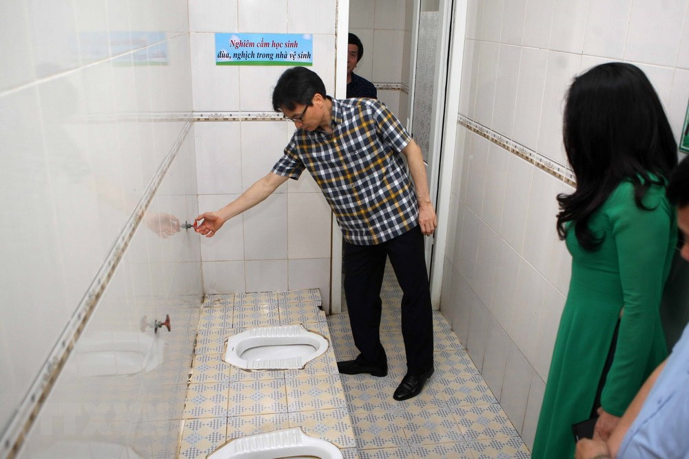 Phó Thủ tướng Vũ Đức Đam kiểm tra khu vệ sinh của học sinh trường tiểu học Đặng Trần Côn, quận Thanh Xuân (Hà Nội). (Ảnh: Thanh Tùng/TTXVN)