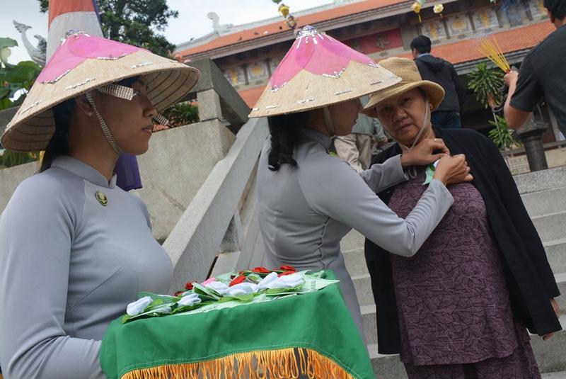 Người phụ nữ lớn tuổi được gắn một bông hồng trắng lên áo.