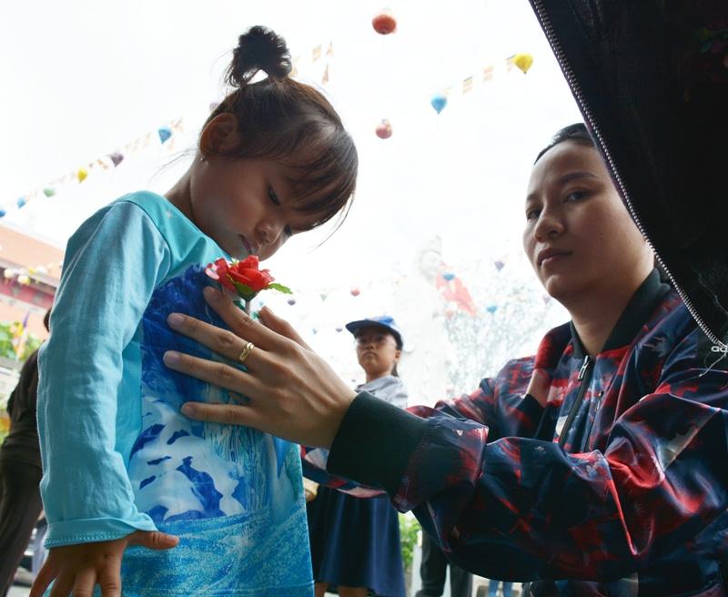 Người mẹ hạnh phúc khi được chính tay gắn bông hồng màu đỏ lên ngực áo con gái.