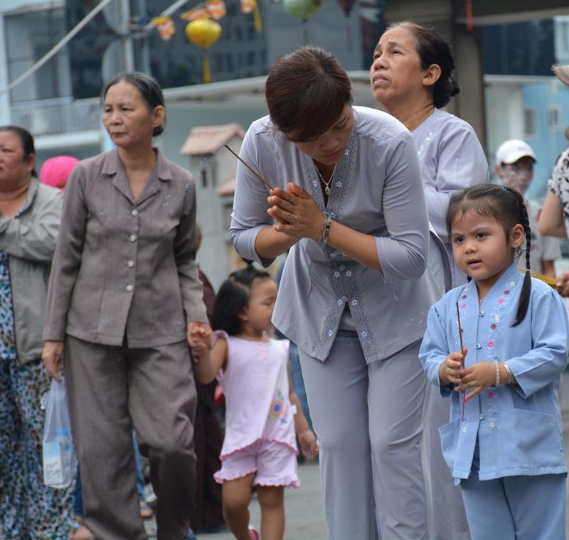 Người mẹ dắt cô con gái 3 tuổi đi chùa ngày lễ Vu Lan.