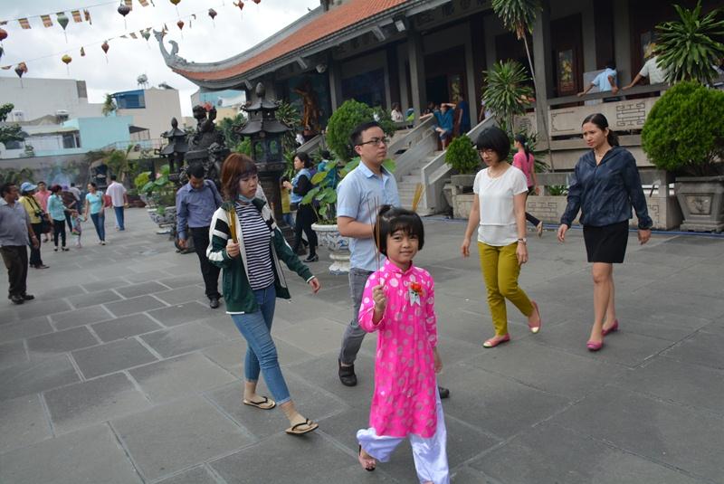 Một em bé được cha mẹ đưa đi lễ chùa Vĩnh Nghiêm.