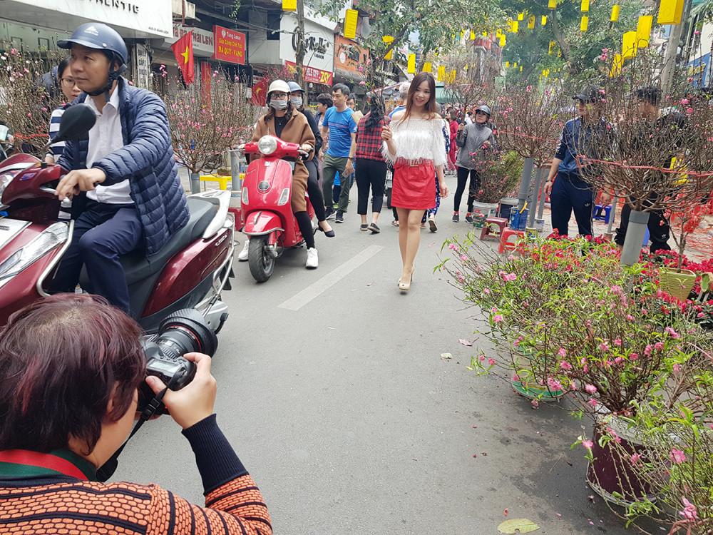 Một cô gái mua cành đào nhỏ để tạo dáng chụp ảnh giữa chợ hoa đông đúc