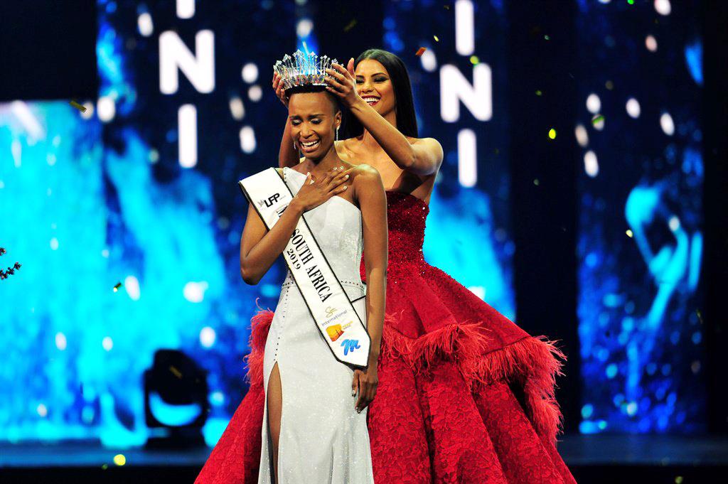 Vượt qua 15 đối thủ trong đêm chung kết Hoa hậu Hoàn vũ Nam Phi 2019 vừa diễn ra, cô gái 25 tuổi Zozibini Tunzi đã xuất sắc đăng quang ngôi vị Hoa hậu. Trong ảnh: Zozibini Tunzi nhận vương miện từ người tiền nhiệm Tamaryn Green - đương kim Á hậu 1 Miss Universe 2018