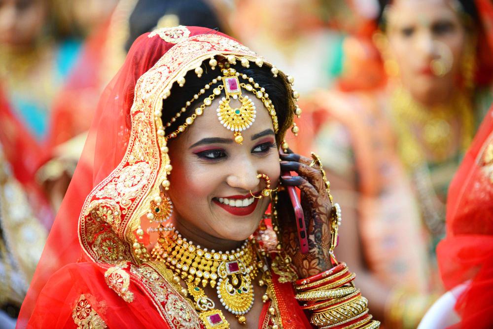 Một cô dâu theo đạo Hindu nói chuyện trên điện thoại trước khi tham gia lễ cưới tập thể ở Surat.