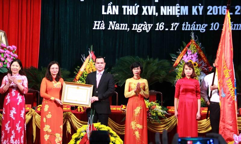 Thừa ủy quyền của Chủ tịch nước, ông Nguyễn Đình Khang (đứng giữa), Ủy viên TƯ Đảng, Bí thư tỉnh ủy Hà Nam trao Huân chương Độc lập hạng Nhất cho Hội LHPN tỉnh Hà Nam