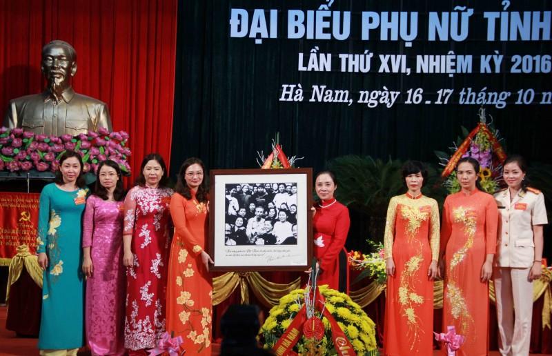 Phó Chủ tịch Thường trực Hội LHPNVN Hoàng Thị Ái Nhiên trao tặng bức ảnh Bác Hồ và các đại biểu phụ nữ, chụp 1950, cho Hội LHPN tỉnh Hà Nam