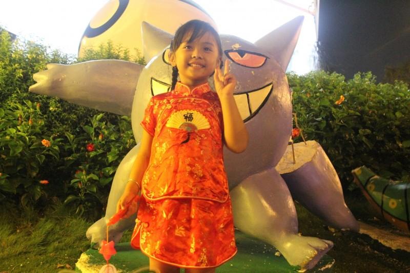 Một bé gái được mẹ dắt đi chơi hồn nhiên tạo dáng trước con pokemon được làm bằng xốp tại phố