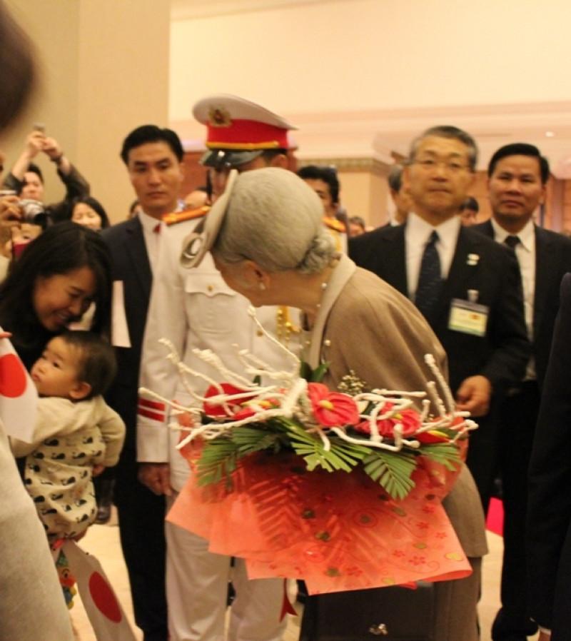 Ánh mắt trìu mến của Hoàng hậu nhìn em bé đang được mẹ địu trước ngực.