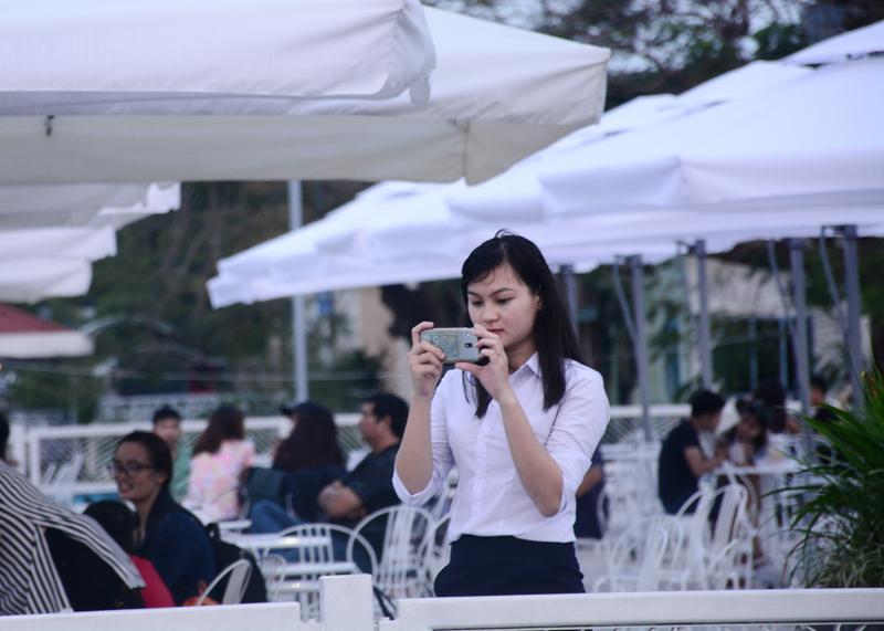 Một cô gái sử dụng điện thoại quay lại cảnh buýt đường sông để làm kỷ niệm.