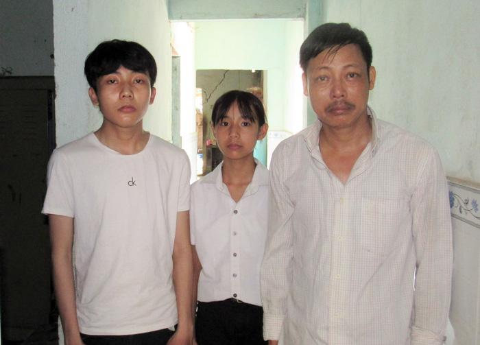 Em Long (bìa trái) cùng cha và em gái