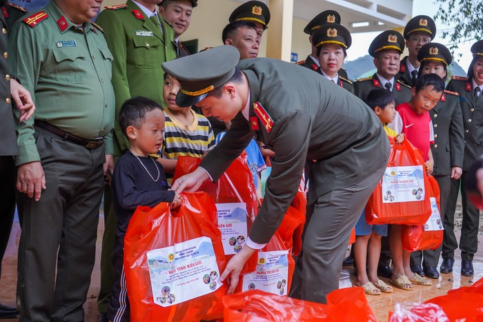 Đoàn viên Đoàn Thanh viên và  Hội viên chi hội phụ nữ phòng Tham mưu Công an thành phố Hà Nội trao những món quà nhỏ, khoác áo ấm cho các cháu