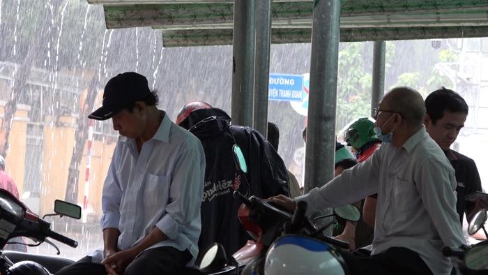 Nhiều người dân TPHCM không mang theo áo mưa phải trú dưới các mái hiên xen đường