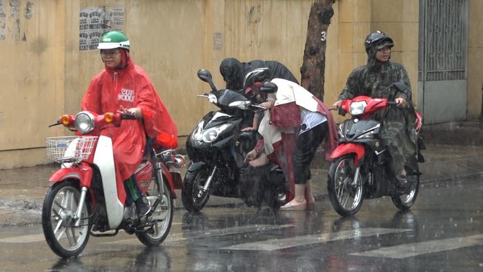 Người dân đang lưu thông buộc phải dừng lại mặc áo mưa vì cơn mưa bất ngờ đổ xuống