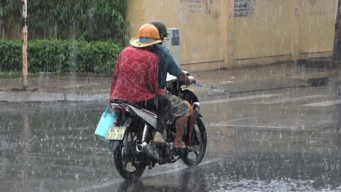 Người không mang áo mưa vẫn dầm mưa về nhà như để cho mát sau bao ngày nắng nóng