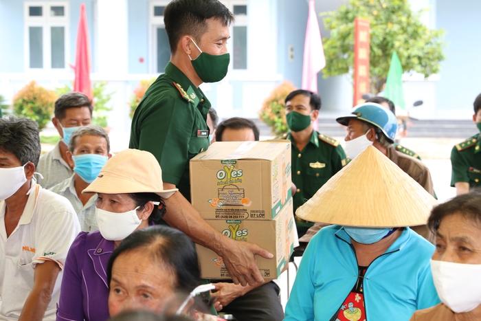 Một chiến sỹ đang trao quà cho người dân vùng biên giới