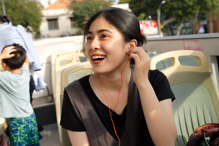 Một nữ du khách đang nghe phiên dịch thuyết minh bằng tai nghe. Ngoài ra phần thuyết minh tiếng Việt thì được phát qua hệ thống loa trên xe với đầy đủ thông tin về các địa điểm mỗi khi  xe đi qua