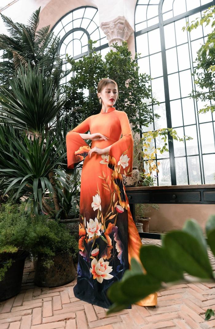 Một thiết kế đầy bắt mắt và nổi bật với gam màu cam ấm là chủ đạo. Bông sen được thêu đầy sắc sảo với những đường chỉ trắng nhẹ nhàng và mềm mại như những nét bút họa lên chiếc áo dài. Chiếc quần màu cam ton-sur-ton tạo nên một tổng thể mang nét cổ điển và đầy ấn tượng với người đối diện