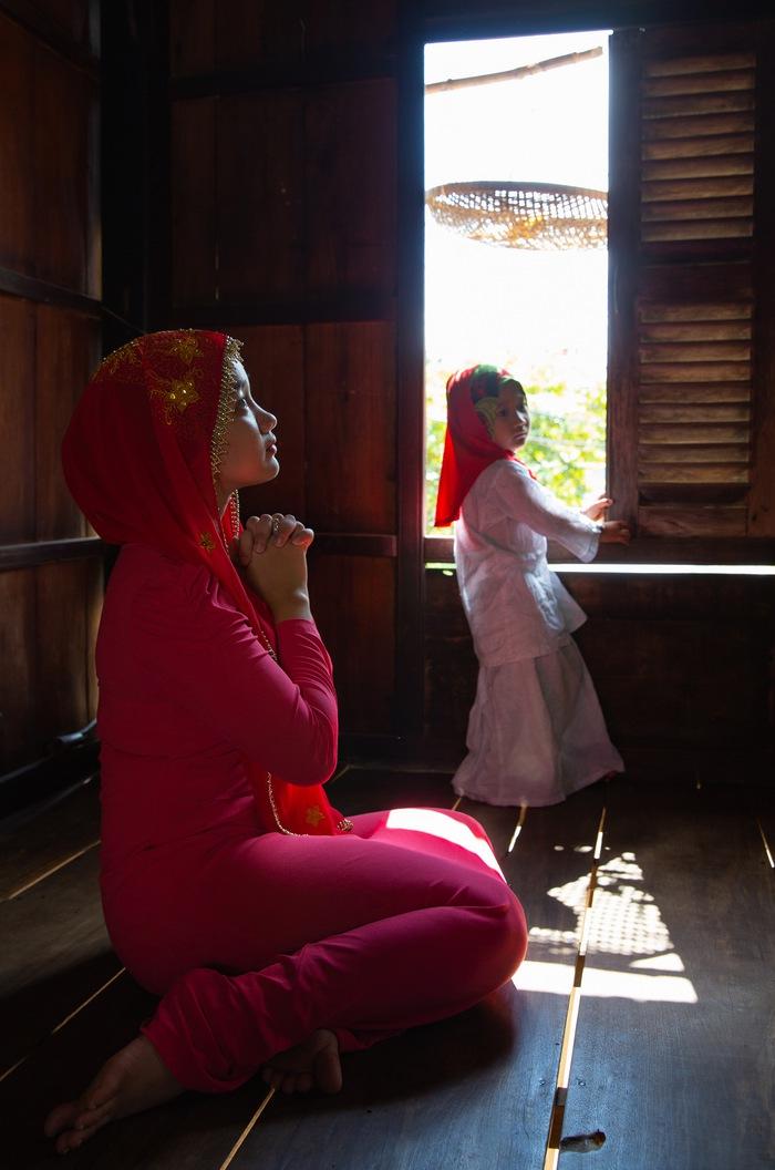 Người phụ nữ Chăm Islam theo đạo Hồi đang cầu nguyện thánh Allah, đưa tay hứng phước lành, mong cầu những điều tốt đẹp cho gia đình- Ảnh: Huỳnh Dũng