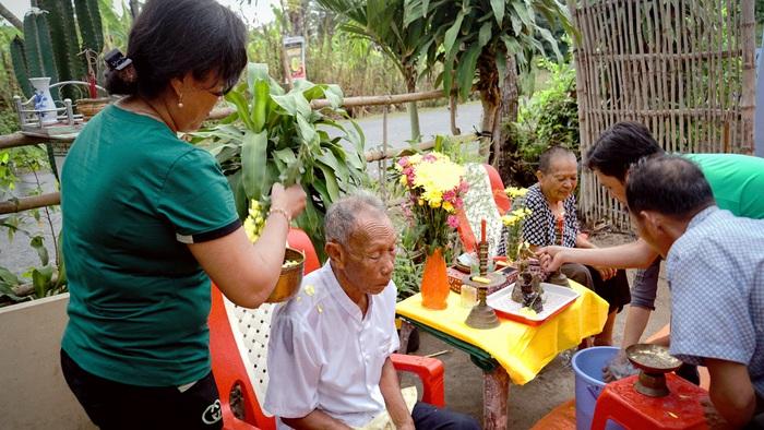 Gia đình người Khơ-me ở TPHCM thực hành nghi thức tắm cho đấng sinh thành ngay sau buổi lễ tắm Phật trong ngày Tết Cholchnam thmay - Ảnh: Hội VHNT Khmer TP.HCM