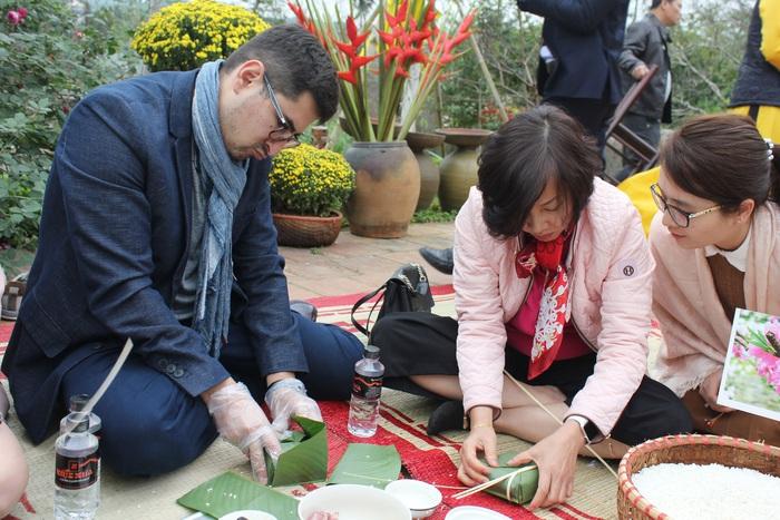 Đại biện lâm thời Chile Gonzalo Gualquil Smoje và bà Trần Thị Bích Vân - Chủ tịch Nhóm Phụ nữ cộng đồng ASEAN gói bánh chưng.